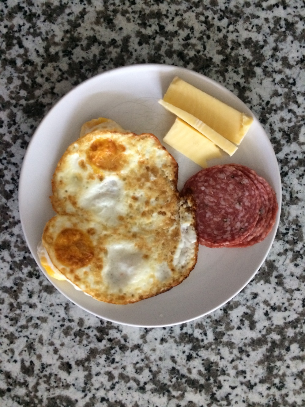 2 eggs over easy cooked in coconut oil, Italian salami, and grass-fed cheese